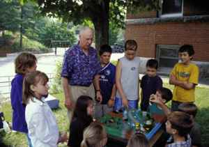 Older_person_shows_how_a_watershed_works_to_a_group_of_school_children
